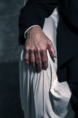 Bloody hand of businessman sitting in white chair.