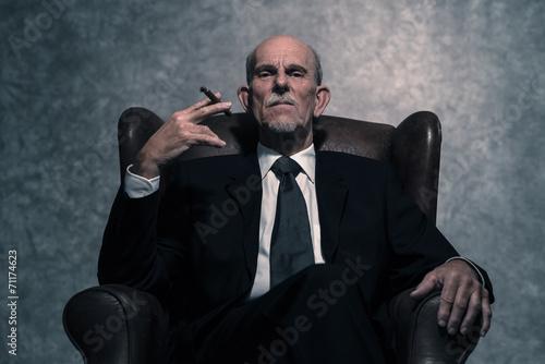 Cigar smoking senior businessman with gray beard wearing dark su - 71174623