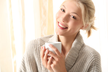 Mädchen im Bademantel mit Tee in der Hand