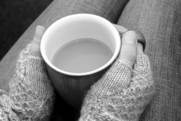 A woman in a cosy jumper holds a cup of tea or coffee on her lap