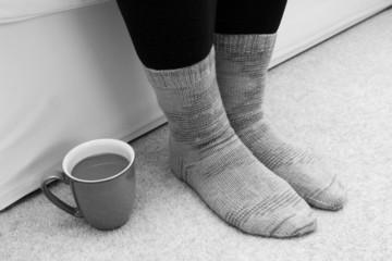 Hot drink on the floor by feet in socks