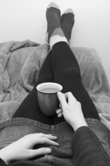 Woman dressed warmly, relaxing with a hot drink