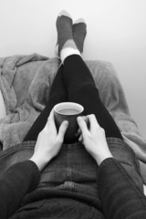 Woman holding a hot drink, relaxing with her feet up