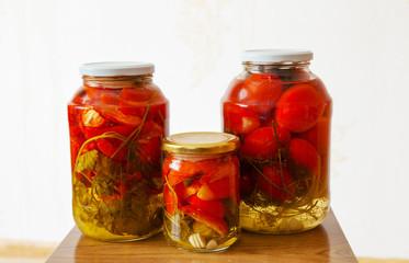 three glass jars with marinated tomatoes homemade