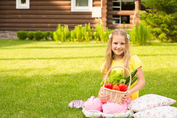 beautiful little girl on green grass with vegetables in basket
