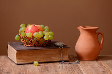 Grapes, apples, books and ceramic carafe