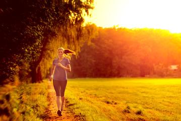 Junge Frau geht im Sonnenaufgang joggen