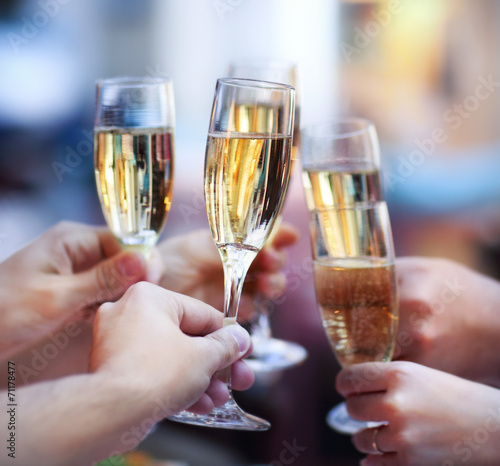People holding glasses of champagne making a toast - 71178477
