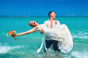 Happy beautiful couple on the beach in wedding dress