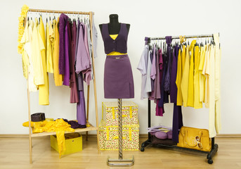 Wardrobe with violet and yellow clothes on hangers and mannequin