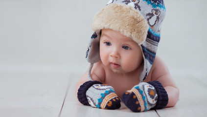 Baby in winter hat and mittens lying on the floor
