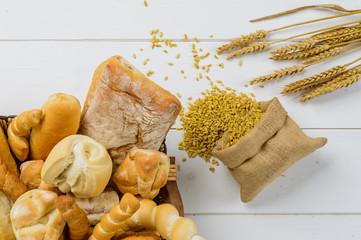 Pane e grano su piano di legno bianco