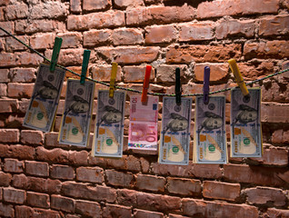 Dollar and euro bills  hanging on a rope