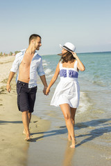Young happy couple walking on beach holding around each other.