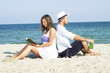 Couple sitting in the sand leaning on each other.