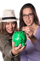 Two Young Girls Putting Coins In Piggy Bank