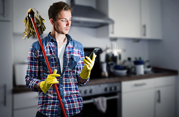Junger Mann lässt sich vom putzen ablenken