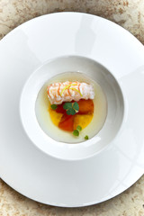 Lobster, tomato confit and juice on a plate