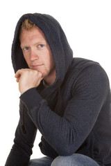 man in hoodie looking close hand chin smile