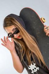 Giovane ragazza tatuata con skate