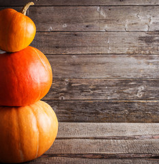 three pumpkins on wooden background