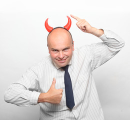 Healthy man with devil horns showing thumbs up.