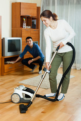 family  cleaning with vacuum cleaner in home