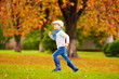 happy boy running in autumn park