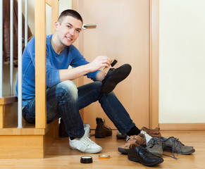 Happy man sitting on stairs and cleaning footwear