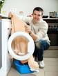 man putting clothes in to washing machine