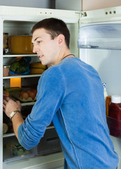 Handsome man looking for something in refrigerator