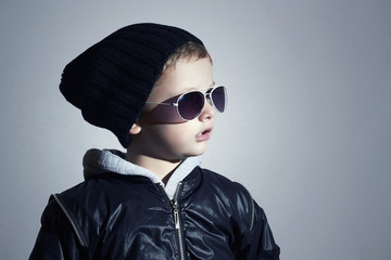Fashionable little boy in sunglasses.Child in Black cap.Winter