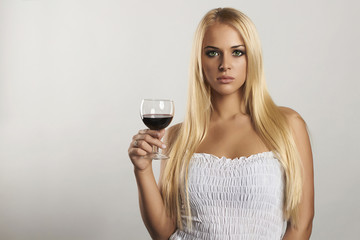 Beautiful blond girl with wine.white dress.red wine.text here