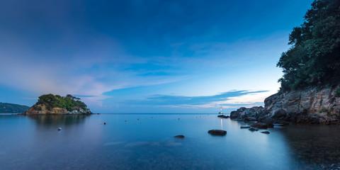small island at sunrise with stoney coast at elba italy