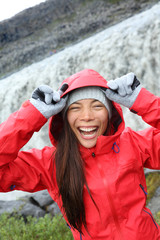 Woman laughing in raincoat by Dettifoss waterfall