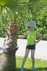 Little boy poses on a background of palm trees