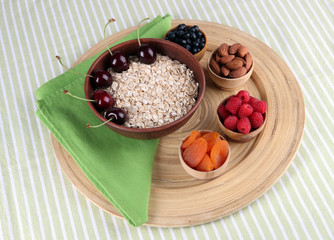 Big round wooden plate with raisins, raspberries, oatmeal, nuts