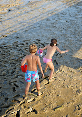 Two children playing in the mud, summer vacation