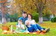 happy family drinking warm tea on autumn picnic