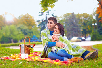 happy couple enjoying autumn picnic in city park