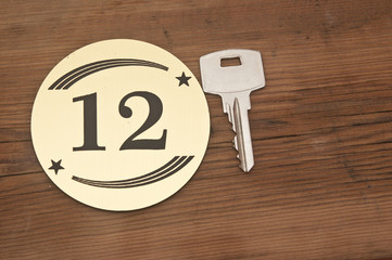 Hotel suite key with room number 12 on wood table