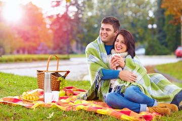 happy couple enjoying autumn picnic in city park