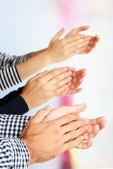 Clapping hands on bright background