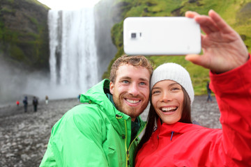 Selfie couple taking smartphone picture waterfall