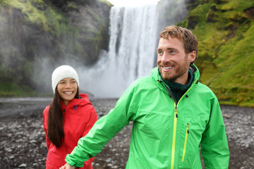 Happy couple holding hands by waterfall outdoors
