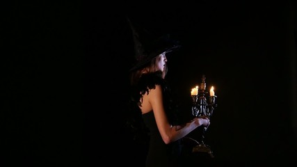 Young sexy witch blows out the candles on a black background