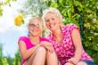 canvas print picture - Familie sitzt im Garten und genießt die Sonne