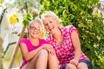 Familie sitzt im Garten und genießt die Sonne