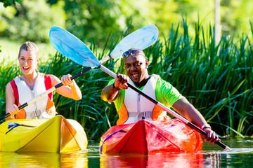 Freunde fahren im Kajak auf Wald Fluss