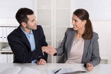 Kunde und Berater geben sich die Hand: sitzend im Büro